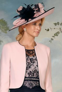 70830 (Condici) A large hatinator in contrasting tones of Flamingo & Navy. The hatinator is placed on an alice band and is worn to one side. The headpiece has anup-turned brim with Sinamay bow detailing and floral feather applique.