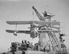 A Supermarine Walrus amphibious aircraft is hoisted on to the catapult on board HMS RODNEY prior to launch. The battleship's superstructure can be seen in the background., Coote, R G G (Lt) Amphibious Aircraft, Ww2 Aircraft, Air Fighter, Fighter Jets, Aviation Image, History Online, Flying Boat, Catapult, Search And Rescue