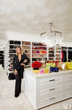 Khloé in her vast master closet; the chandelier is by RH, and the ceiling is lined in a Schumacher wallpaper.