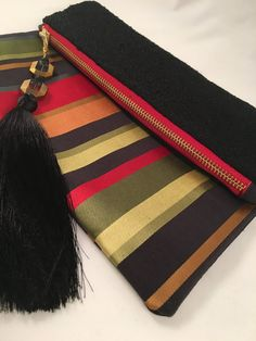 Vibrant stripes in shades of crimson, orange and lime adorn this foldover color blocked clutch.  - cooper & oliver