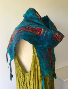 This nuno felted wool and silk scarf is a perfect cosy neck warmer. Super soft merino fibre in shades of turquoise and navy blue have been felted into a red patterned printed silk habotai fabric there is also a blue printed silk fabric on the reverse side which can be seen bubbling through the felted wool. It can be worn in several different ways as shown on the photos. There are tassels at each of the short ends with one tassel featuring a little felted flower at each end. The scarf…