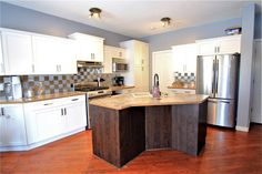 Large working island with eating bar. All stainless steel appliances including double door fridge & gas stove. Diamond Realty & Associates Ltd. All Stainless Steel, Stainless Steel Appliances, Selling Real Estate, Gas Stove, Double Doors, Home Buying, Open House, Island, Bar