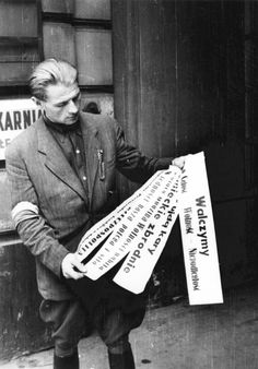 Warsaw rebel holds a poster in front of house 11 in Moniuszki street, august 1944 - pin by Paolo Marzioli