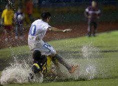 Tarmorley Thomas (li.) vom Inselstaat Antigua und Barbuda kämpft im WM-Qualifikationsspiel mit Mario Rodriguez auf pitschnassem Rasen um den Ball.