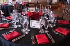 black table cloths, red plates, silver cutlery & white custom napkins!