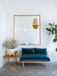 Blue velvet couch in front of a great indoor window. We love the wooden couch table and the green plants.