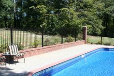 Iron Fence Around a Pool in Conjunction with a Brick Knee Wall and Columns