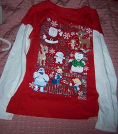 Rudolph the Red Nosed Reindeer Girls Bling Shirt Size 14She will love celebrating Christmas in this adorable blingy Rudolph shirt by Justice. Layered look shirt is red with white sleeves. Front features Rudolph, Santa, Dolly, Clarice, Elephant, Sam the Snowman, Bumble, Charly the Jack in the Box & Hermy the Elf. The names are in silver glitter letters.   Shirt is a girls size 14  Also available in a size 12. You must specify what size or the size 14 will be shipped.  New with tags