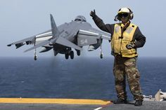 A picture released by the US Navy shows Aviation Boatswain's Mate (Handling) 2nd Class Christiana Marszalek signaling as an AV-8B Harrier takes off from the amphibious assault ship USS Kearsarge (LHD 3) on March 29, 2013 in the Mediterranean Sea. (Photo/CFP)