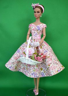 Garden Delight fashion for Poppy Parker, Posable Silkstone and similar sized12 inch fashion dolls  This romantic summer dress features an off-the-shoulder bodice with full skirt in soft pleats and is made from fine cotton fabric in a beautiful pastel flower print. Defining the waist is a detachable pink silk belt with silver-toned square buckle. The bodice of the dress is lined, the seams of the skirt are fully finished and enclosed. The dress fastens at the back with tiny pink buttons over…