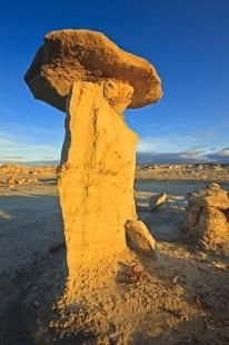 A flat rock sits on top of a pinacle called a hoodoo, an eroded column of rock, much softer than the cap rock. There are many hoodoos found in the Bisti Badlands of New Mexico, USA.
