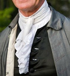 The 18th-century man almost always wore some sort of neck cloth, whether fashionably dressed or at labor.The cravat was one of many forms of neckwear. It was a narrow length of white linen that could be adorned on its ends with lace, fringe, or knots. It was worn wrapped about the throat and loosely tied in front.