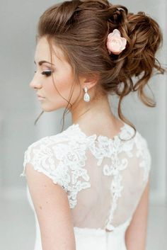 Rose Accented High Low Bun - 30 Best Wedding Bun Hairstyles - EverAfterGuide