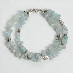 "Handmade gemstone aquamarine bracelet features 2 strands of semi-precious aquamarine gemstone chips, sterling silver accent beads, wire band, and lobster claw clasp. 8"" in length. Add a necklace, pend"