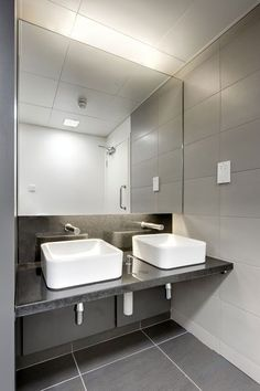 Simple Yet Modern Commercial Bathroom Sinks - Plain white sinks on a black counter with silver fixtures are basic enough but a closer look yields a modern aesthetic with the sinks above the counter and the spigot a simple cylinder.