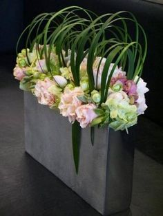 Pretty Flower Arrangement in a long, narrow vase with curved palm fronds to look like basket handles