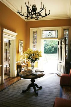 lovely foyer.. I want that chandelier and I would remove the rug to show the pretty floors
