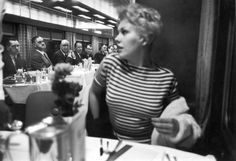 """1956   """"Eyes right"""" is executed with near-military precision by men aboard a New York-bound 20th Century Limited train as movie star Kim Novak eases into her seat in the dining car. Originally published in the March 5, 1956, issue of LIFE."""
