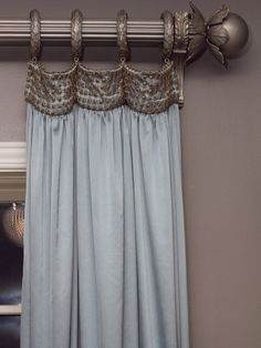 Embellished drapery heading with decorative hardware.