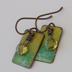 Yellow gradually flows to green on the front surface of these copper drops. Similar in construction to another set in our shop, but without the hints of blue color the original one has. The metal rectangles have been enameled with ground glass using a torch flame - the back of the drops remains in the torched copper tone as seen in the 4th pic. A small yellow and brown speckled glass sequin droplet is wrapped with aged copper wire and hangs on the front of the enameled piece. Ear wires are…