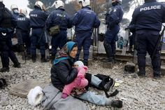 A refugee breastfeeds her baby behind a Greek police cordon as she waits to cross the Greek-Macedonian border near the village of Idomeni, Greece December 4, 2015. REUTERS/Yannis Behrakis
