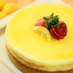 Lemon Cheesecake - A lemon glaze over a sour cream topping on top of a luscious and creamy cheesecake.