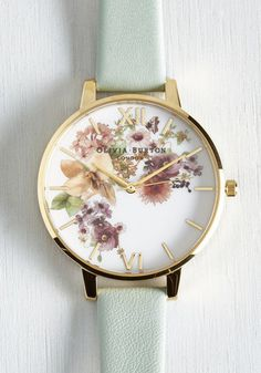 No matter the weather, you enjoy a lovely look accessorized with this charming Olivia Burton watch! An arrangement of blooms in muted tones pattern the face of this gold watch, while a mint leather band makes it versatile enough to don again and again.