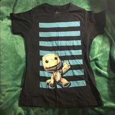 NWOT XL Little Big Planet Sackboy Girly Tee Never worn. I never could beat this game even with three other players, someone always died on that level with the electrical crap. The Dia de los Muertos level owns, though. Great music! This is a promo tee from when the game was released, so if you're a fan, nab it! Rare! LittleBigPlanet Tops Tees - Short Sleeve