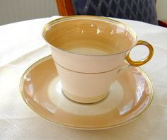 This is a Shelley China, England art deco design cup and saucer in the Regent shape with a design called Swirls in the brown colorway with gold trim made 1940-1952. The tea cup and saucer is made of b