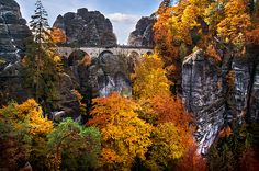 BASTEI BRIDGE IN AUTUMN TIME. SAXON SWITZERLAND by JENNY RAINBOW/.  Bastei in German translates as bastion and you can easily see why this name was chosen for this towering rock formation, situated on the River Elbe near Dresden in the German Free State of Saxony. Towering almost 200 meters over the river below, Bastei was formed by water erosion over a million years ago. #JennyRainbowFineArtPhotography #SaxonSwitzerland #Nature #Autumn #Bastei #Beauty #Canvas #FramedPrints