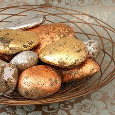 Shimmering Stones Centerpiece  Add some shimmer to your #Thanksgiving table by coating ordinary rocks with gold, silver, and copper leaf. Give the rocks a rustic look by leaving some of the surface exposed.
