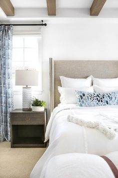 A dark gray nightstand accented with a brass nailhead trim sits on a tan rug beneath a window covered in blue curtains hung from and oil rubbed bronze rod.
