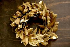 Gilded magnolia leaves formed into a ring make this luxe yet classic wreath the perfect adornment for a festive home!