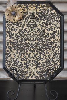 Black distressed frame with flower embellishment.  Black iron stand included.