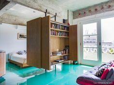 Armário de madeira funciona como divisória entre sala de estar e quarto.