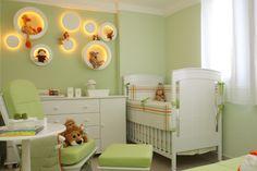Decoração de quarto de bebê em tons de verde e branco com nichos iluminados.