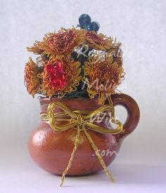 Wire sculpture of a miniature bouquet of sunflowers and butterflies in a clay pot