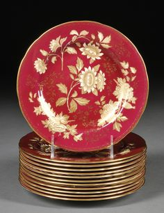 Wedgwood Bone China Ruby Tonquin Side Plates, England, mid-20th century, each with gilded and cream enameled floral design to a ruby ground.