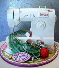 Singer Sewing Machine    3-D mostly edible sewing machine. the sewing machine is the cake, with fondant and white chocolate decoration. All of the accessories and material are completely edible white chocolate , fondant, etc. Another masterpiece by Cory