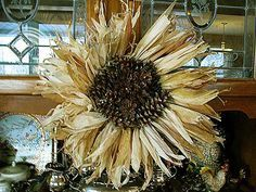 Corn husk sunflower wreath. a great idea! Corn husk wreath with pine cones attached to the inner circle.