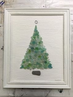 Soft turquoise beach sea glass tree on vintage canvas, set in vintage frame, painted soft creamy white. The base of tree is rectangle beach stone, topper is metal found on beach, and the tree is a col