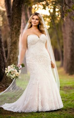 This romantic plus size dress from Carrie Johnson Bridal features lace detail and a soft hourglass shape. Linear lace on the bodice creates curves in the waist while a very subtle beaded empire waist draws attention to the bride's face.