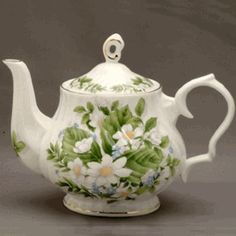 Tea pot with white flowers & green leaves.