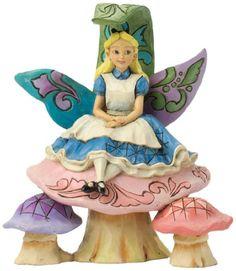 Statue of Alice sitting on a mushroom.