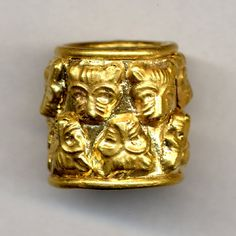 Gold finger-ring, formed of a broad flat band of gold with a ring of gold soldered at either end; to the outside of the band are soldered two rows of hollow stamped lions' masks, placed in opposite directions, six in each row. 1550 BC - 1050 BC Late Bronze Age