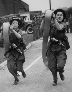 1942, Female firefighters during a skills demonstration.   25 Stunning Vintage Photographs Of Female Firefighters