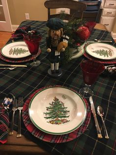 Tartan wool blanket serves as the foundation for Stewart chargers and Spode Christmas Tree plates. Nutcracker with bagpipes and greenery are the featured centerpiece.
