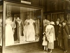 Visitors to the London Museum examining Queen Victoria's wedding clothes
