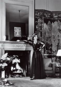 Coco Chanel in her Paris apartment by the fireplace