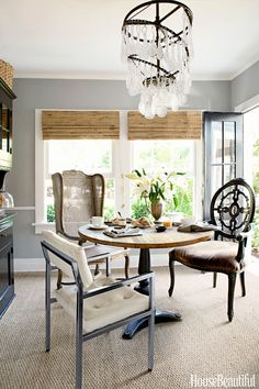 "In the breakfast room of her Hollywood Hills farmhouse, Tobi Tobin arranged a trio of vintage chairs, all from different periods. She used simple bamboo shades from Target, painted the walls Farrow & Ball's Lamp Room Gray, ""and — voilà — a modern farmhouse!"" she says.   - HouseBeautiful.com"
